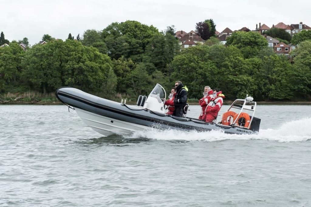 powerboat training - grey rib with men in full waterproofs travelling at speed