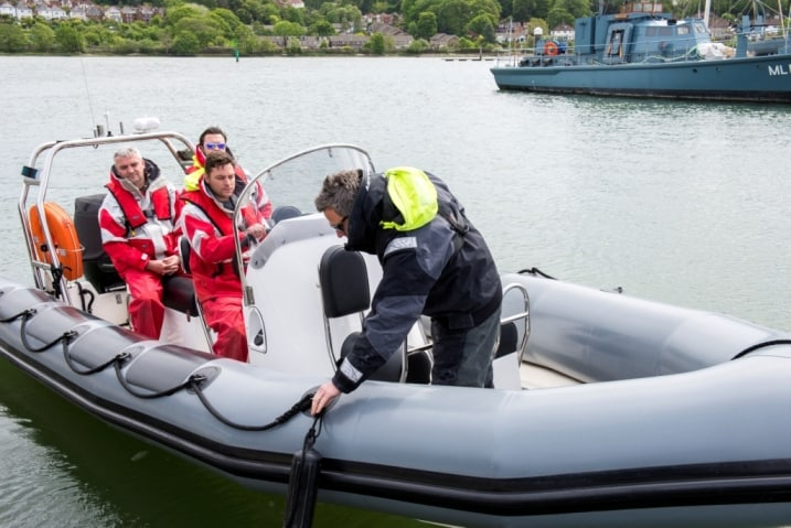 rya intermediate powerboat course - instructor picking up a fender from the side of a grey rib