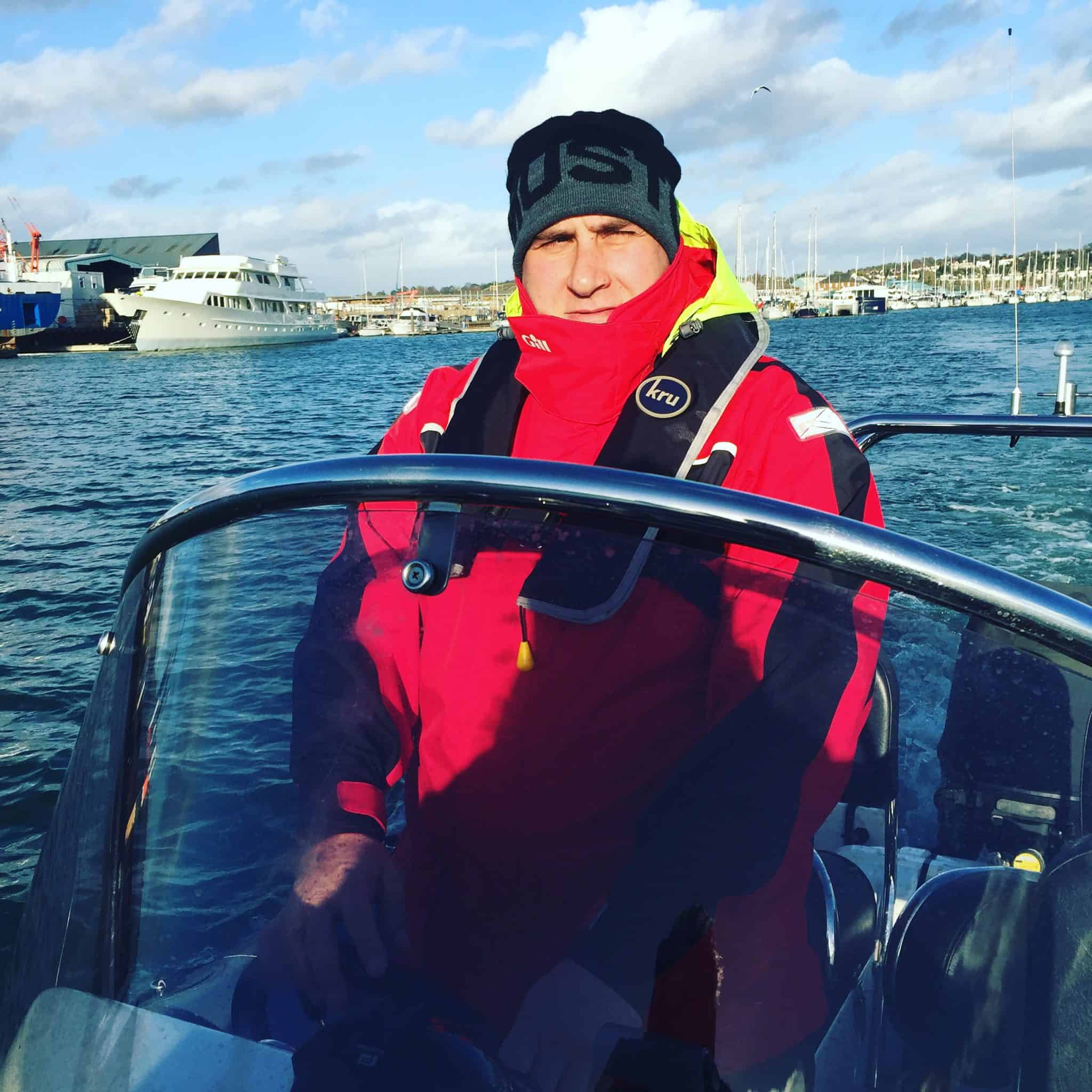 RYA MCA Advanced course - man in red waterproofs driving a powerboat in the sun