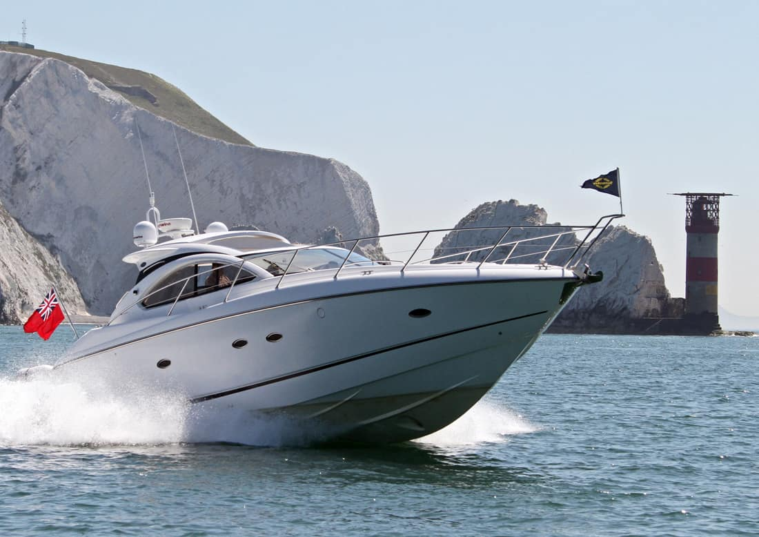 yachtmaster power rya coastal skipper motor boat travelling with wake past The Needles on the Isle of Wight