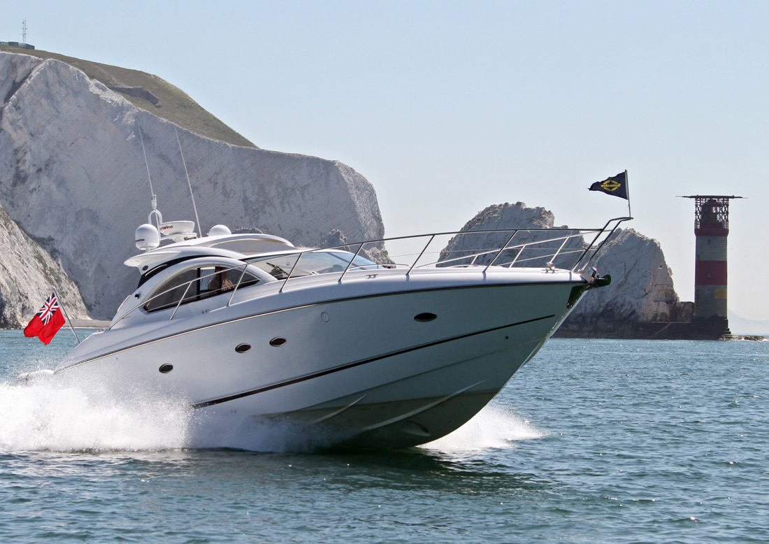 rya coastal skipper - motor boat travelling with wake past The Needles on the Isle of Wight
