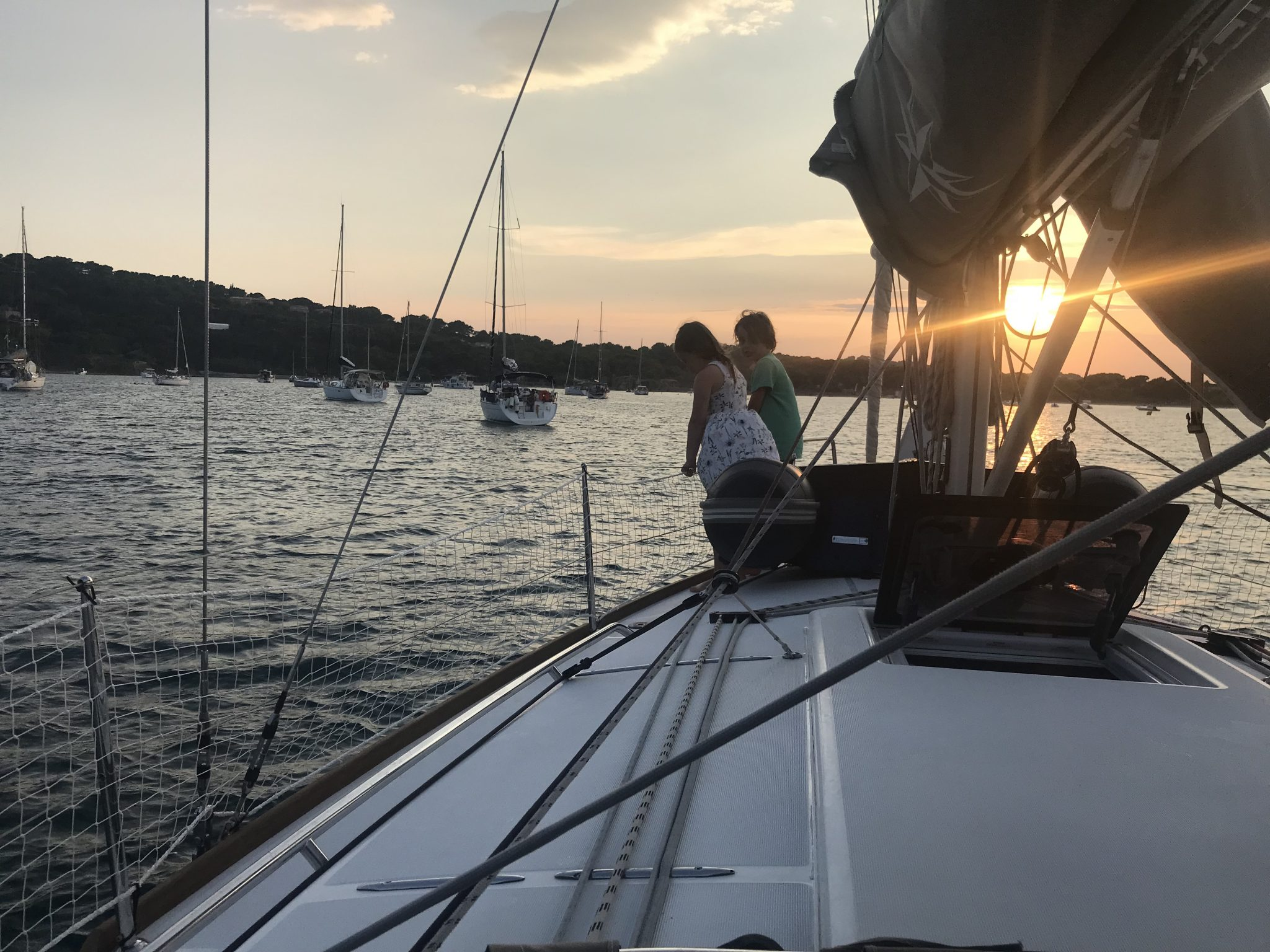yacht charter - children stood on front of a yacht on a summer sailing holiday at sunset
